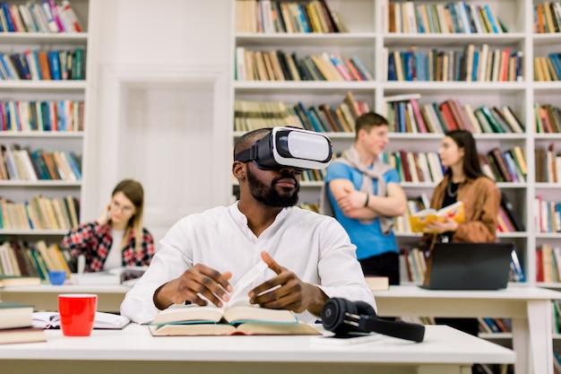Zwarte kerel die de vr-hoofdtelefoon van bril draagt, boek leest en informatie van virtuele werkelijkheid gebruikt, zittend in moderne bibliotheek. groep studenten studeren en praten met elkaar