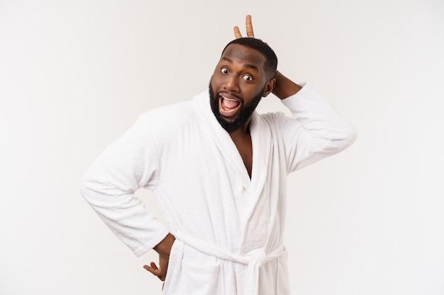 Zwarte kerel die een badjas draagt die vinger met verrassing en gelukkige emotie richt. geïsoleerd.