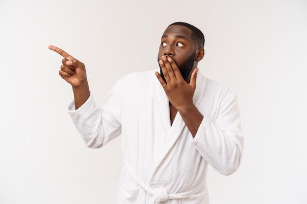 Zwarte kerel die een badjas draagt die vinger met verrassing en gelukkige emotie richt.