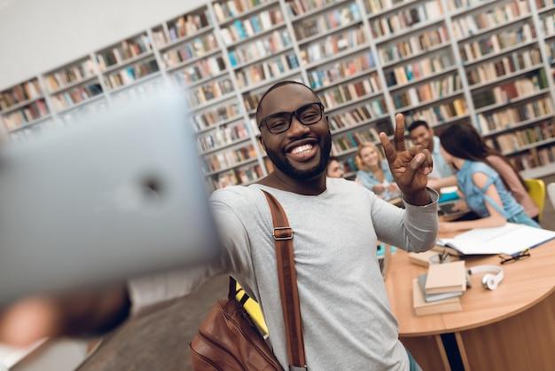 Zwarte kerel die selfie op telefoon in schoolbibliotheek nemen.