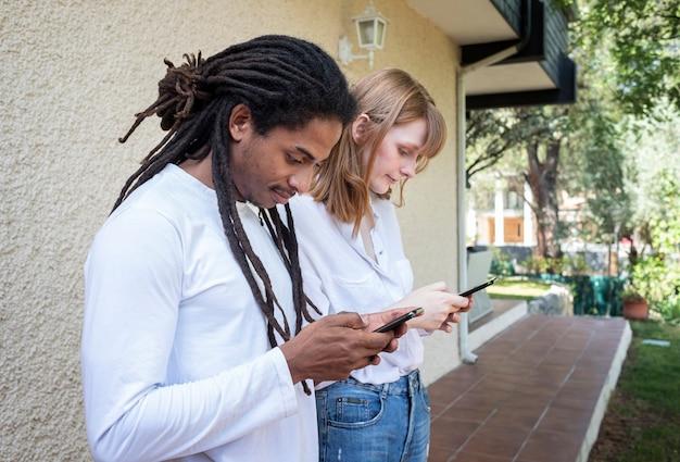 Zwarte kerel en kaukasische meisje kijken en chatten met de mobiele telefoon.