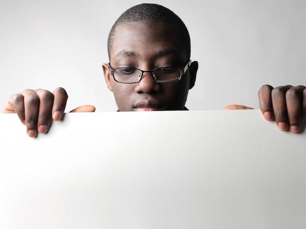 Zwarte kerel kijkt neer op een bord