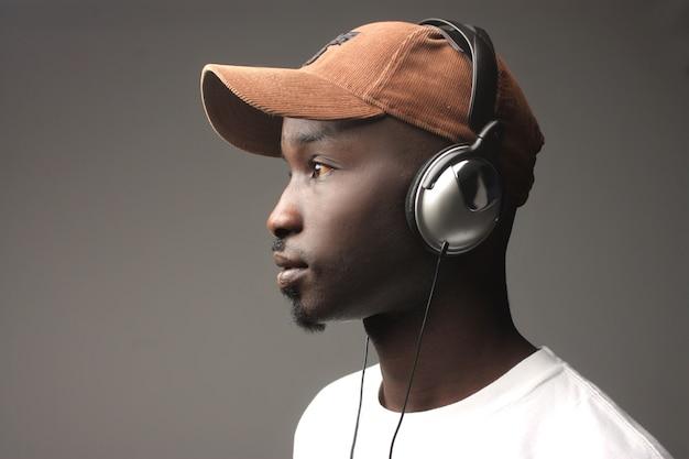 Zwarte kerel op profiel het luisteren muziek met oortelefoons