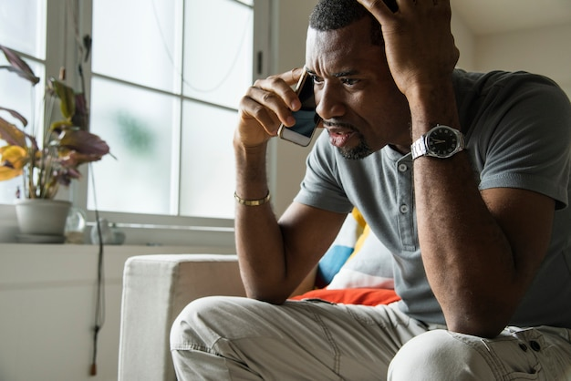 Zwarte kerel sprekende telefoon met boze emotie