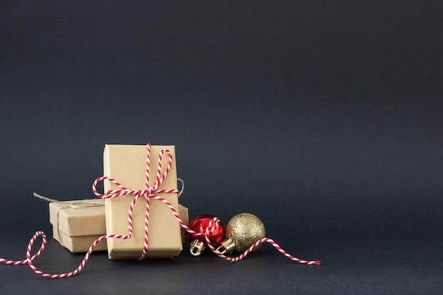 Zwarte kerstachtergrond met geschenkdozen en kerstversieringen