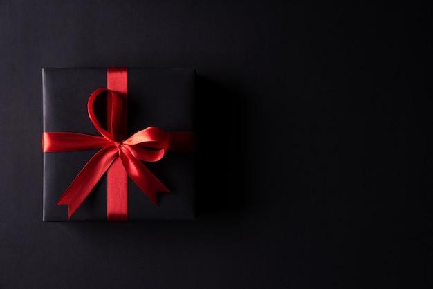 Zwarte kerstdozen met rood lint op zwart