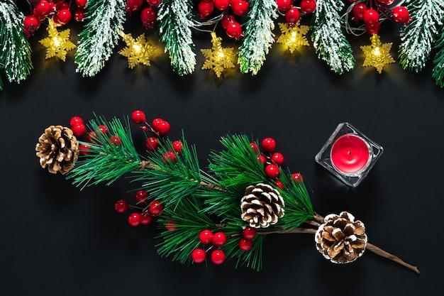 Zwarte kerstkaart, new year's achtergrond met groene fir tree takken, dennenappels, rode bessen en kaars.