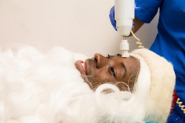 Zwarte kerstman die cosmetische ingrepen in de kuuroordkliniek doet. cosmetische ingrepen in kuuroordkliniek.