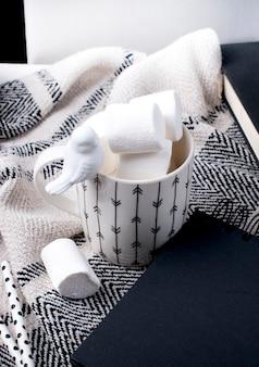 Zwarte kladblok, cup en plaid op witte achtergrond