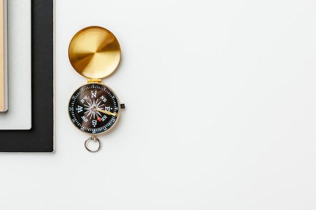 Zwarte kladblok voor nautische notities en gouden kompas op een witte tafel achtergrond