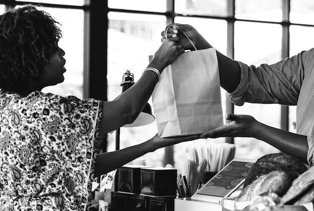 Zwarte klant die bakkerijproducten koopt