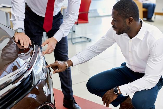Zwarte klant man stelt vragen over koplampen van auto in dealer