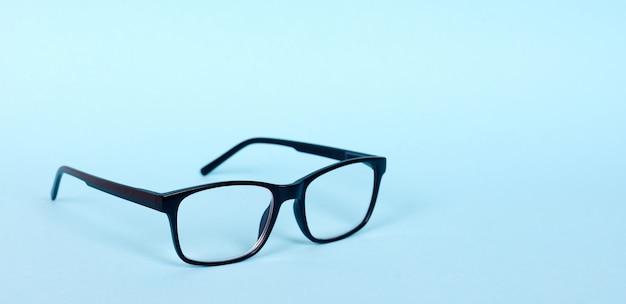 Zwarte klassieke bril, medicijn contactloos. geïsoleerd op blauwe achtergrond. kopieer ruimte.