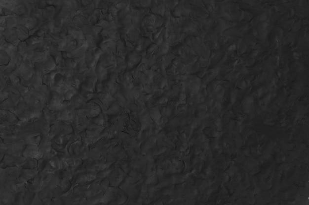 Zwarte klei getextureerde achtergrond in abstracte diy creatieve kunst minimale stijl