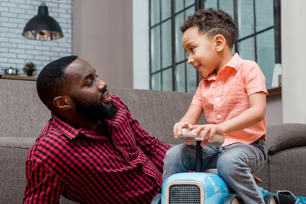 Zwarte kleine jongen speelgoedauto rijden met vader