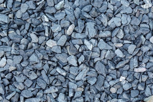Zwarte kleine weg stenen achtergrond, donkere grind steentjes steen textuur naadloze textuur, graniet, marmer