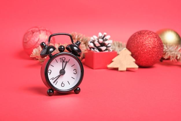Zwarte kleine wekker en kerstdecor op rood oppervlak