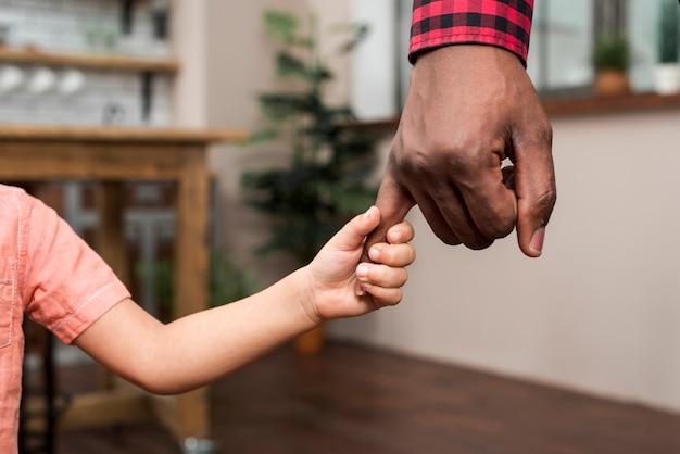 Zwarte kleine zoon met vaders hand