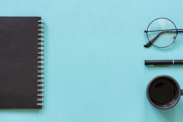 Zwarte kleur kladblok, kopje koffie, bril, pen op blauw