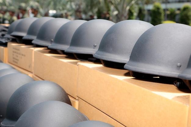 Zwarte kleuren militaire helmen bereiden zich voor om aan soldaten te geven
