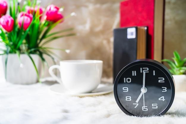 Zwarte klok en kopje koffie, koffietijd in de ochtend