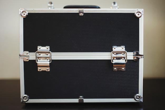 Zwarte koffer met aluminium verstevigde hoeken en baleinen.