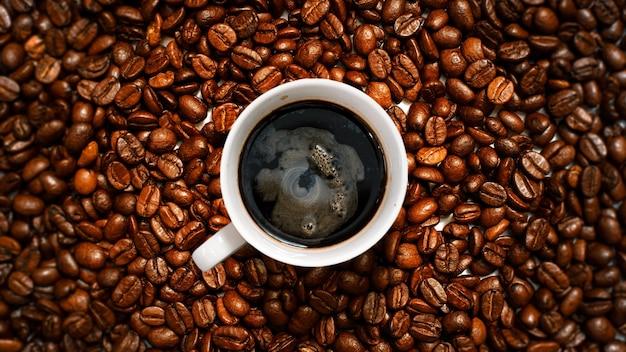 Zwarte koffie bovenaanzicht op koffiebonen