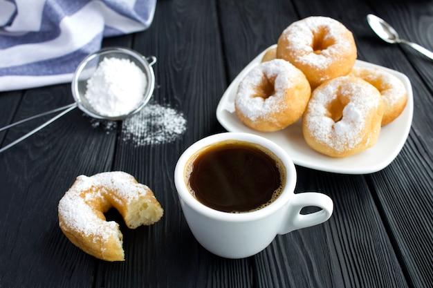 Zwarte koffie en donuts met poedersuiker op de zwarte