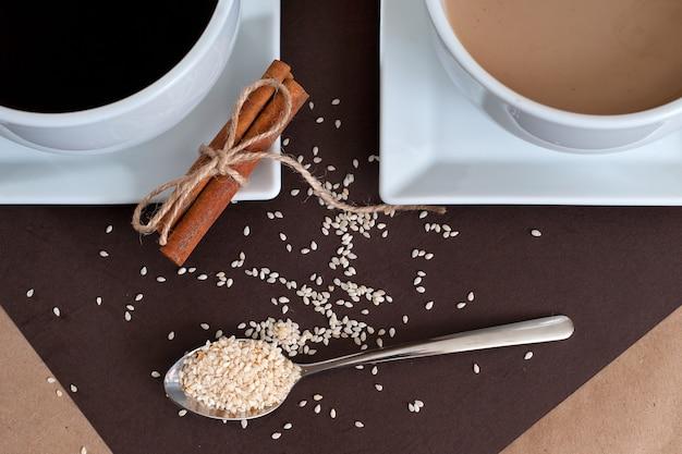 Zwarte koffie en koffie met melk in witte kopjes. kaneel en sesam.