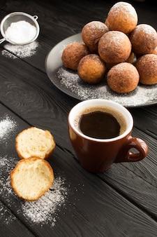 Zwarte koffie en zelfgemaakte kwarkdonuts op donker