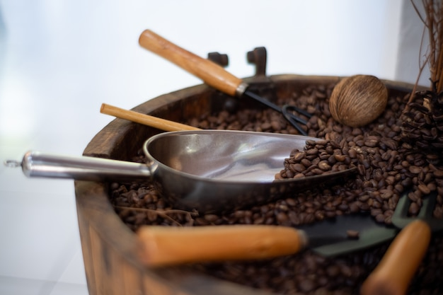 Zwarte koffie gebrande koffiebonen en koffiedik in houten lepels en kaneelstokjes