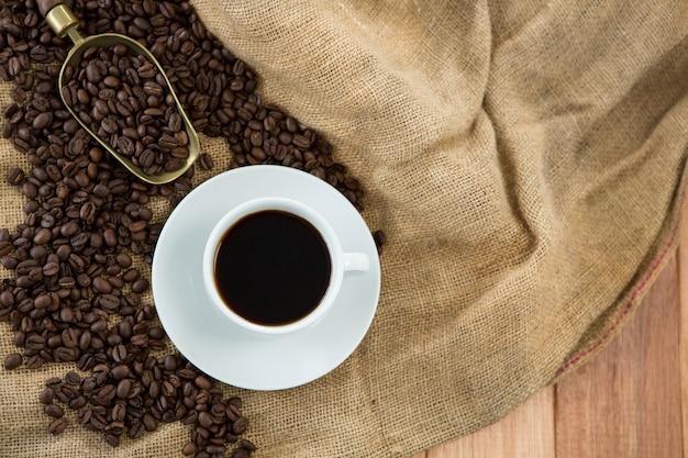 Zwarte koffie, geroosterde bonen en schep op zak