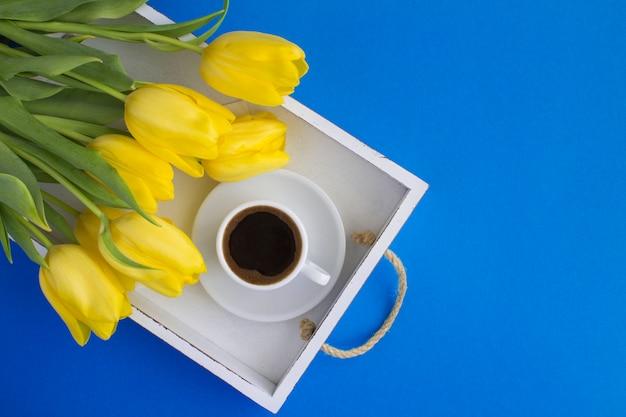 Zwarte koffie in de witte kop en gele tulpen op het witte houten dienblad op het blauwe oppervlak. bovenaanzicht. kopieer ruimte.