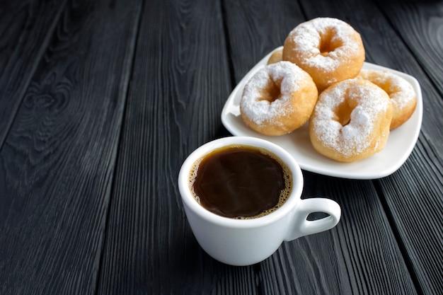 Zwarte koffie in de witte kop en zelfgemaakte donut met poedersuiker