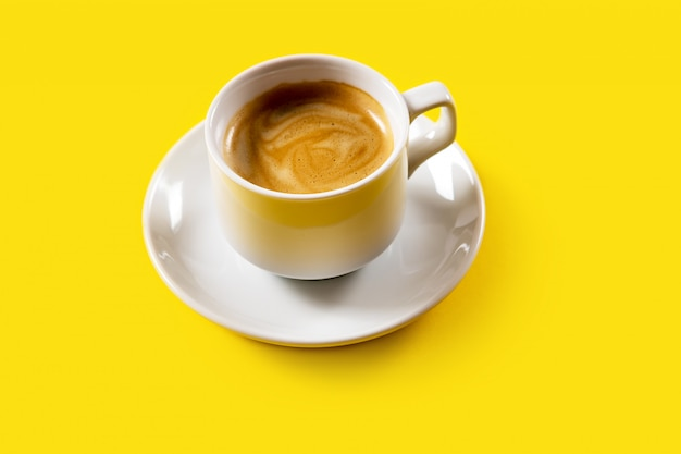 Zwarte koffie in een kop op geel