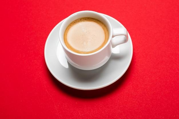 Zwarte koffie in een kopje op een rode ondergrond