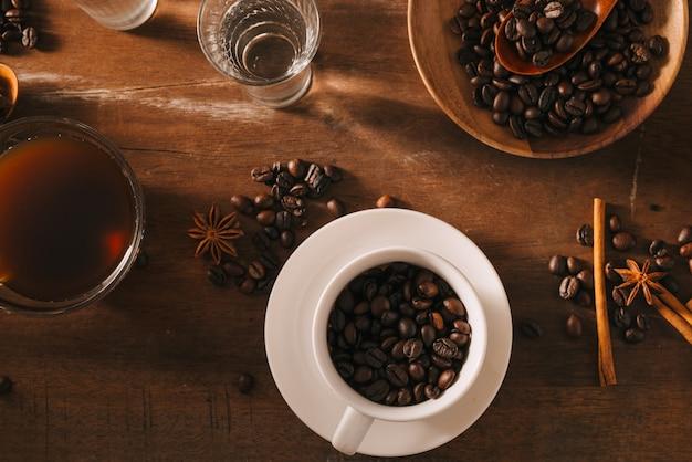 Zwarte koffie in een kopje op het oppervlak van koffiebonen in een compositie met toebehoren