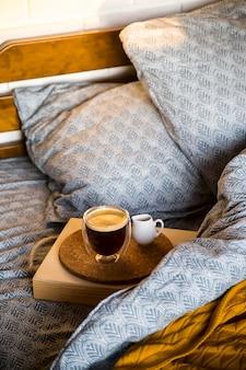 Zwarte koffie in een transparante kop in bed in de herfstochtend