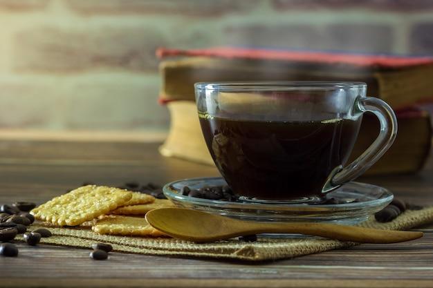 Zwarte koffie in helder glas cup en koffie bonen met crackers en oud boek op houten tafel.
