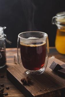 Zwarte koffie in het glas met stoom over houten oppervlak, honing en donkere chocolade