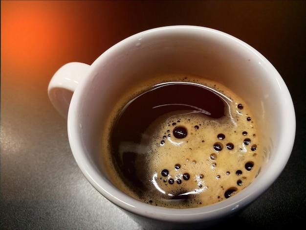 Zwarte koffie in kop dichte omhooggaand op lijst
