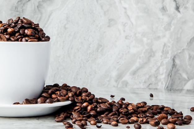 Zwarte koffie in kop en koffiebonen op marmeren achtergrond. bovenaanzicht, ruimte voor tekst