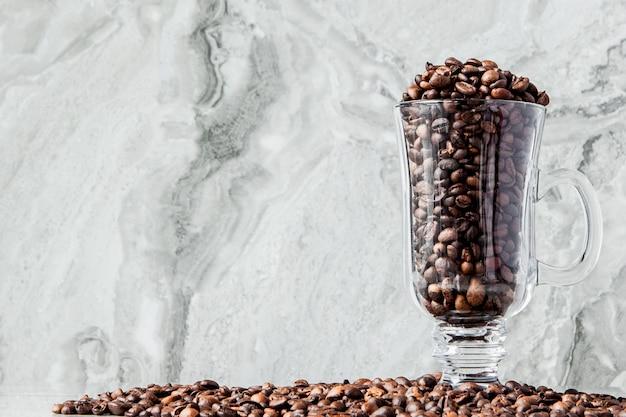 Zwarte koffie in kop en koffiebonen op marmeren achtergrond. bovenaanzicht, ruimte voor tekst.