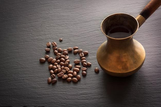 Zwarte koffie in oud koper cezve en koffiebonen op zwarte lei