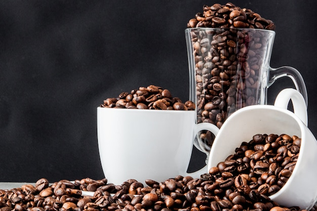 Zwarte koffie in witte kop en koffiebonen op zwarte achtergrond. bovenaanzicht, ruimte voor tekst