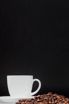 Zwarte koffie in witte kop en koffiebonen op zwarte achtergrond.