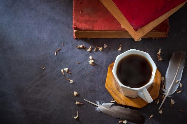 Zwarte koffie in witte kop en oude boeken met veer en gedroogde bloembloemblaadjes geplaatst op de marmeren tafel en ochtendzon.