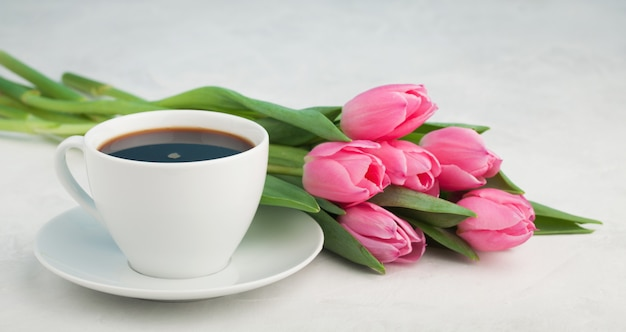 Zwarte koffie in witte kop en tulpen.