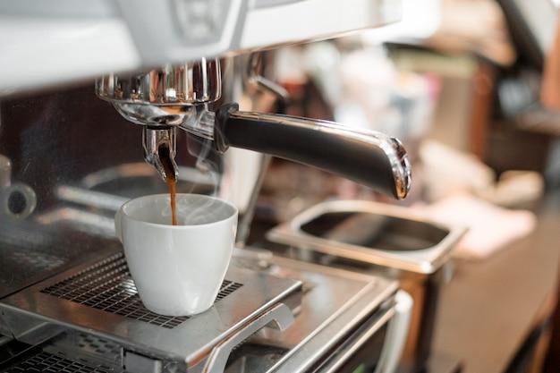 Zwarte koffie in witte kop gezet op koffiezetapparaat