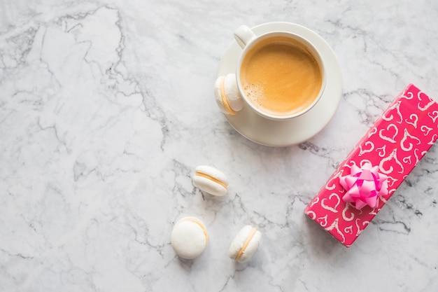 Zwarte koffie met bitterkoekjes koekjes, huidige doos. kopje koffie en kleurrijke macaron. zoete bitterkoekjes.